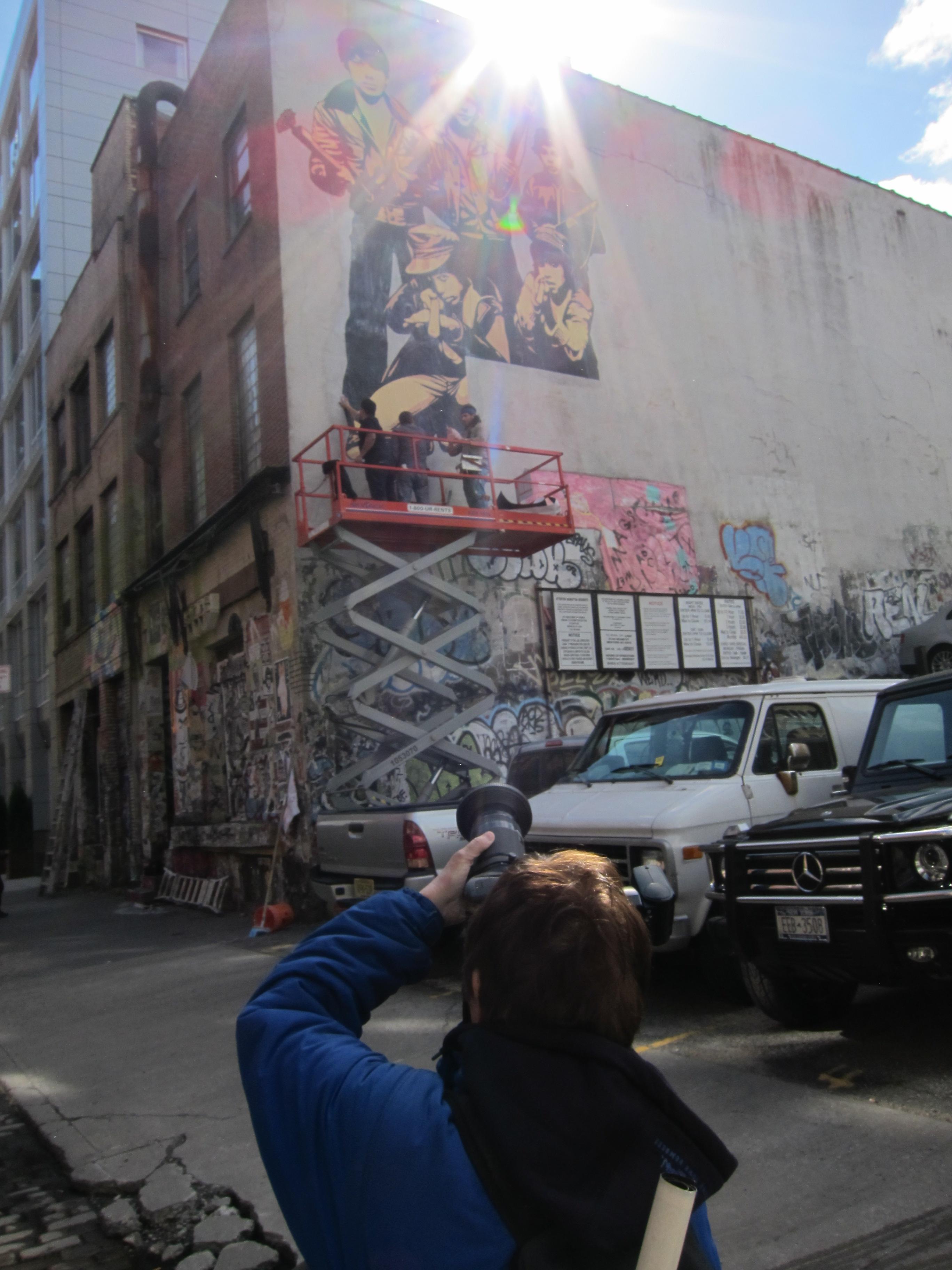 Martha shoots Shepard making a mural of the image Martha shot.