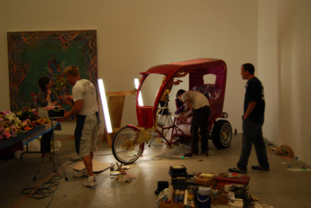 Dzine and his diligent crew finish up his flamboyant rickshaw-esque vehicle. A work by Ryan McGinness hangs in the background.