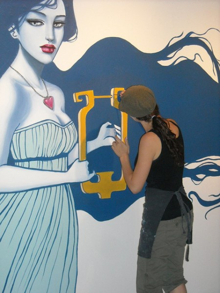 Sarah Joncas working on wall mural