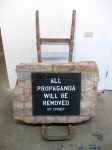 'Propaganda'. 2011. Acrylic on brick. The wall comes from the recently-demolished Whitten's Timber building (Peckham, South London) which housed the Area 10 Project Space, used to organise art events and as studio spaces for artists including War Boutique