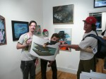 Tre' Packard and Aaron Glasson of PangeaSeed holding up a Josh Keyes print with a fan.