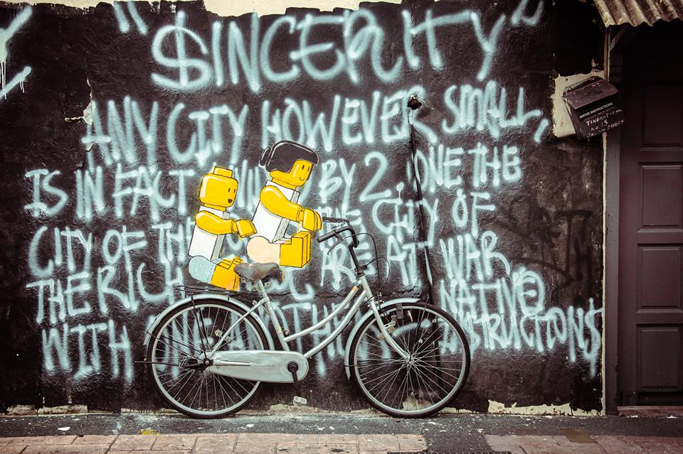 """Ernest Zacharevic in Malaysia. """"$INCERITY"""" : Any city however small, is in fact divided by 2, one the city of the poor, the other of the rich. These are at war with one another. - NATIVE IN$TRUCTION$ (Quote from The Republic by Plato)"""