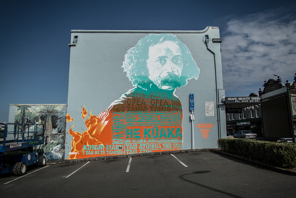 Askew in New Zealand with a tribute mural to Ralph Hotere. Photo via Graffuturism.